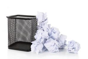 lata de lixo cheia de malha de arame com papel amassado espalhados. foto