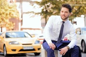 bom jovem empresário sentado na pedra