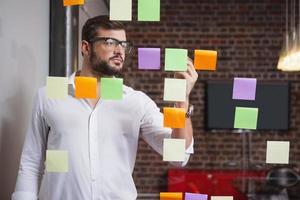 empresário casual, escrevendo em notas autoadesivas foto