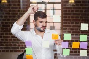 empresário casual olhando notas autoadesivas foto