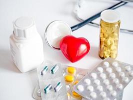 coração com estetoscópio e comprimidos foto