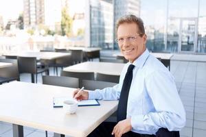 empresário bonito sentado à mesa foto