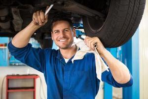 mecânico examinando debaixo do carro foto