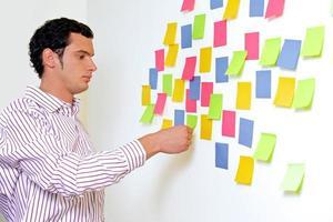 empresário, olhando para a parede de notas autoadesivas
