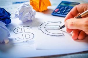 mão desenhando um cifrão e euro sinal foto