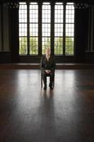 empresário sentado na grande sala vazia foto
