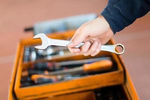 mão do mecânico segurando uma chave