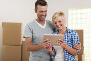 casal feliz usando tablet digital durante a mudança de casa foto