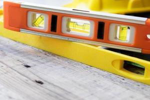 nível de construção vermelho e amarelo na mesa de madeira foto