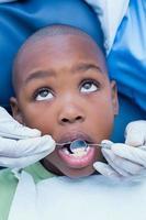 menino tendo seus dentes examinados pelo dentista foto