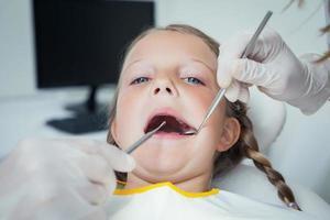 close-up da menina, tendo os dentes examinados foto