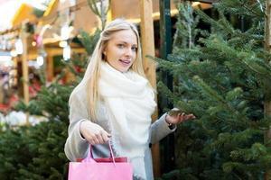 menina escolhe uma árvore de natal foto