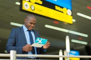 empresário americano africano, verificando seu bilhete de avião foto