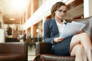 empresária lendo documentos no café foto