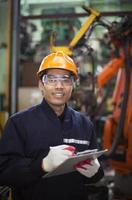 jovem no capacete, escrevendo na área de transferência na fábrica foto