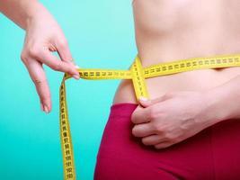 dieta. mulher de fitness cabe garota com fita métrica, medindo a cintura foto
