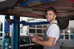 mecânico de automóveis em pé debaixo do carro foto