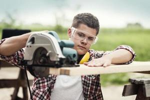 trabalhador da construção civil serrar pranchas de madeira foto