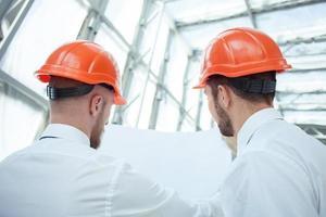 alegres jovens construtores estão trabalhando no plano de construção foto