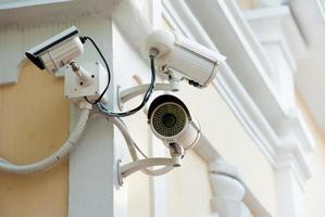 vista frontal de três câmeras de segurança na parede de concreto