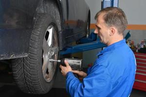 roda de carro em mudança do auto mecânico foto