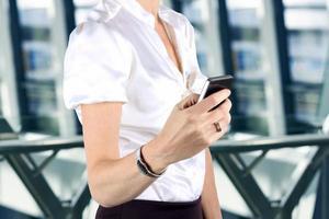 empresária, segurando e usando o telefone móvel esperto foto