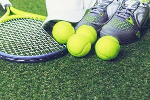 raquete de tênis e nova bola de tênis na quadra verde foto
