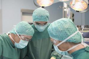 três médicos em cirurgia foto