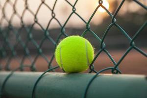 bola de tênis na quadra fechar ao pôr do sol foto
