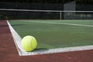 uma única bola de tênis no canto de uma quadra de tênis foto