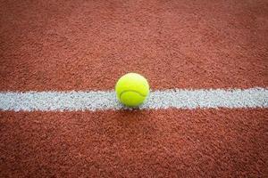 bola de tênis na linha da quadra foto
