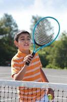 garoto segurando uma raquete e bola de tênis foto