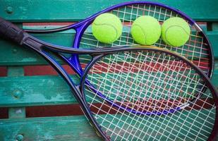 raquete de tênis com bolas na quadra de tênis foto