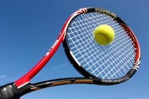 raquete de tênis batendo a bola foto