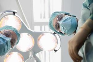 cirurgiões sob luzes de cirurgia no bloco operatório foto