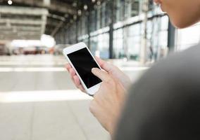 usando telefone inteligente móvel no aeroporto. foto