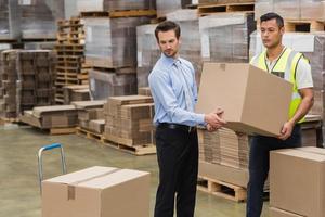 trabalhador de armazém e gerente carregando uma caixa juntos