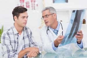 médico mostrando raios x para seu paciente foto