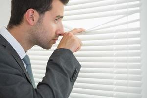 empresário calmo bonito espiando através das cortinas de rolo foto