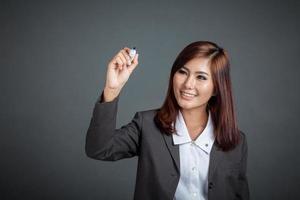 sorriso de menina de negócios asiáticos escrever no ar