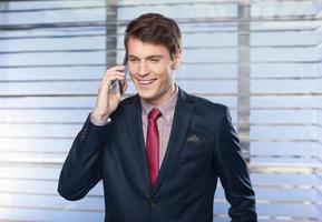 empresário bonito ao telefone, olhando feliz foto