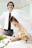sorrindo noiva assina certidão de casamento foto