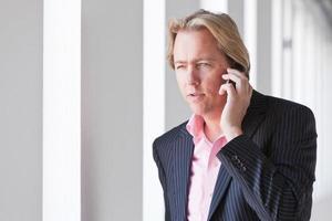 homem de negócios, ligando com o celular no escritório branco. foto
