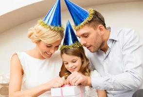 família feliz em chapéus de festa azul, abrindo a caixa de presente