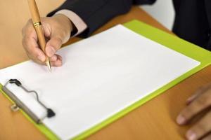 homem escrevendo no papel em branco
