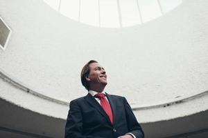satisfeito feliz jovem empresário em pé sob o domo da luz. foto