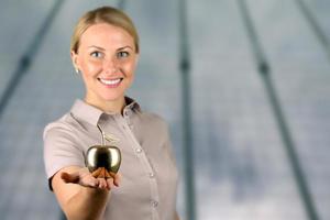 empresária em pé e segurando a maçã dourada na mão.