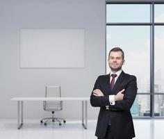 empresário bonitão sorridente em um terno preto com braços cruzados.