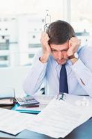 empresário estressado com a cabeça nas mãos foto