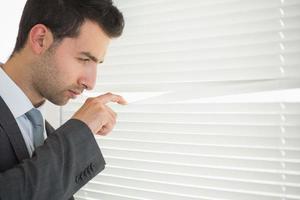 empresário carrancudo bonito espiando através das cortinas de rolo foto
